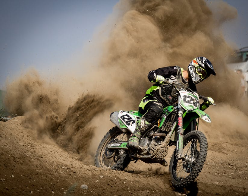 A man riding a motorcycle down a dirt road